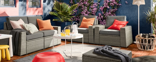 SOLLERÖN sofa and two armchairs with dark grey cushions, white coffee table and wicker basket.