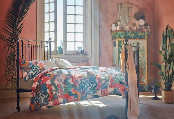 Solstråler gennem et åbent vindue i et rustikt soveværelse. På den sorte jernseng er farverigt sengetøj med blomster og fugle.