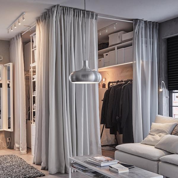 Solution penderie ouverte avec rideaux gris clair GUNRID, portant noir et coussins gris sur canapé blanc.