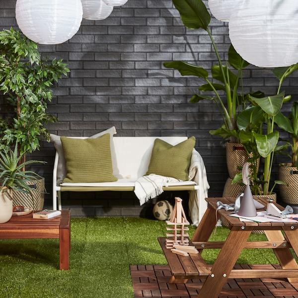 그레이 벽돌 벽을 배경으로 안락한 좌석 공간, 푸른 화초, SOLVINDEN 솔빈덴 LED태양광펜던트등이 있는 야외 공간.