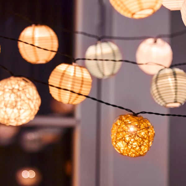 다양한 종류의 SOLVINDEN 솔빈덴 LED체인조명이 창문 밖에 걸려 있고 불이 켜진 모습.