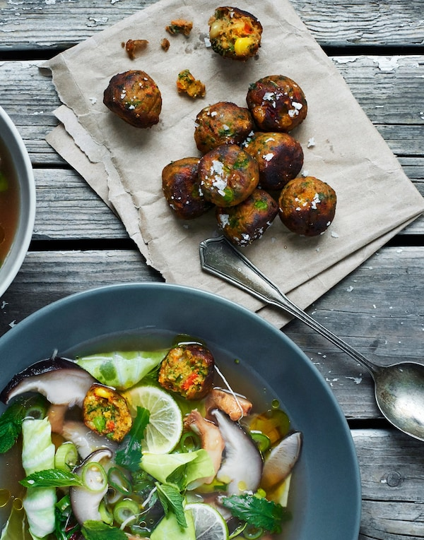 Some fried plant-based veggie balls lying beside a soup bowl with lots of greens and some veggie balls in it.