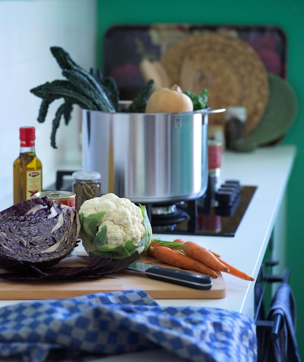 Some vegetables on a work surface beside a cooking hob with a large saucepan.
