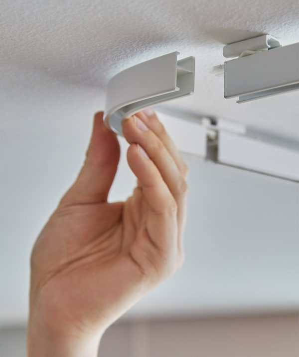 Someone clicking together the corner pieces of an IKEA VIDGA track system mounted on the ceiling.