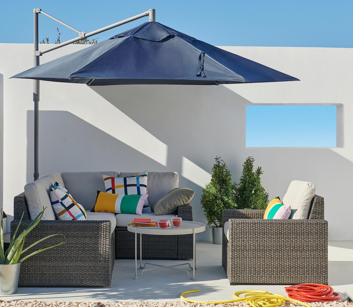 Sommerliche, weiße Terrasse mit blauem Sonnenschirm, Ecksofa, Sessel, weißem Terrassentisch & Duftkerzen.