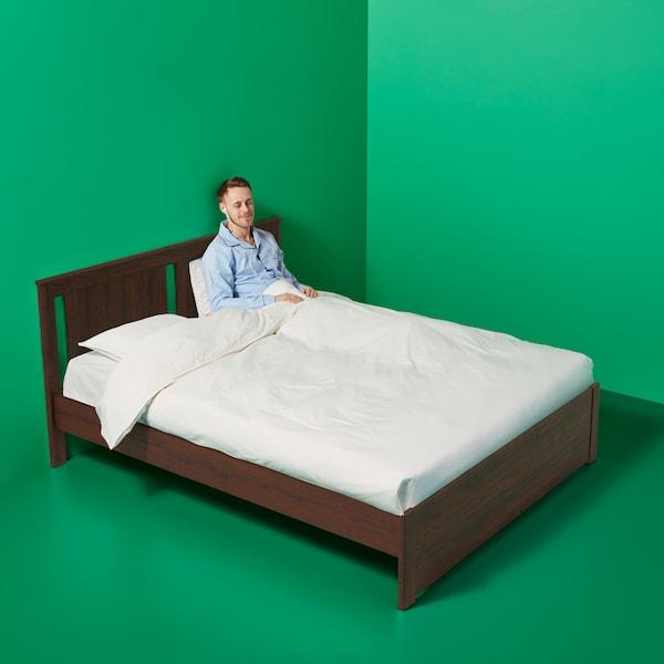 ผู้ชายสวมชุดนอนสีฟ้านั่งอยู่บนเตียง SONGESAND/ซองเงซันด์ สีน้ำตาลในห้องที่มีพื้นสีเขียวและผนังสีเขียว