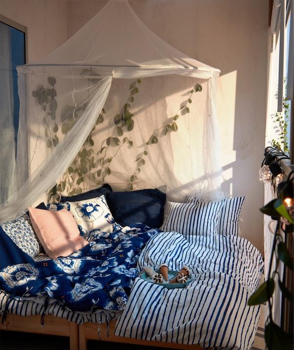 Sonnendurchfluteter Balkon mit Doppelbett und blauweißer Bettwäsche, darüber SOLIG Netz weiß.