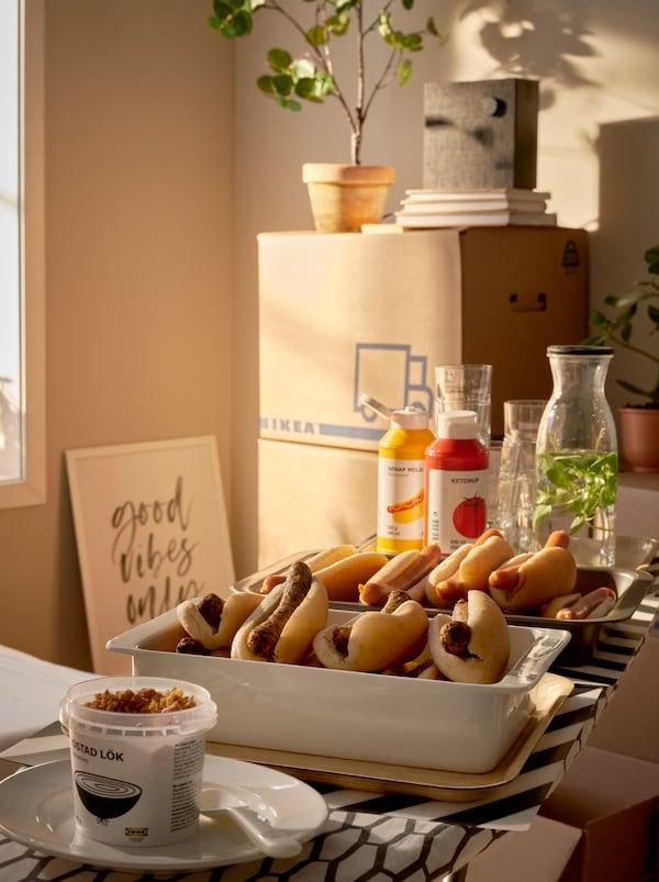 Sonnendurchfluteter Raum mit gestapelten JÄTTENE Umzugskartons und einem Hotdog-Büfett auf Tabletts, die auf einem DÄNKA Bügelbrett stehen.