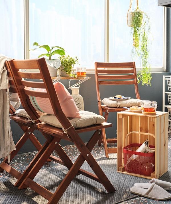 Sonniger Balkon mit einer Sitzecke aus zwei ÄPPLARÖ Stühlen und einem KNAGGLIG Kasten als improvisiertem Tisch.