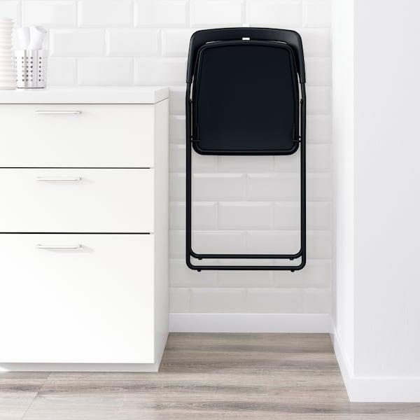 Sort NISSE klapstol hænger på en hvid væg på et smalt sted mellem en væg og et skab.