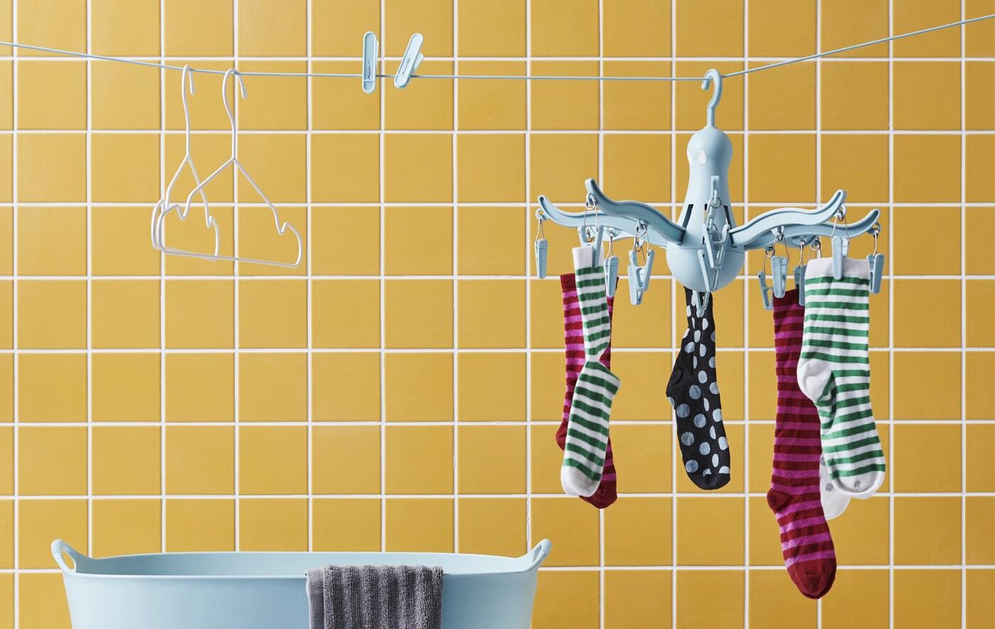 Șosete pe un uscător de rufe suspendat albastru, cleme de haine și umerașe pe o sfoară de haine pe un perete de dale galbene.