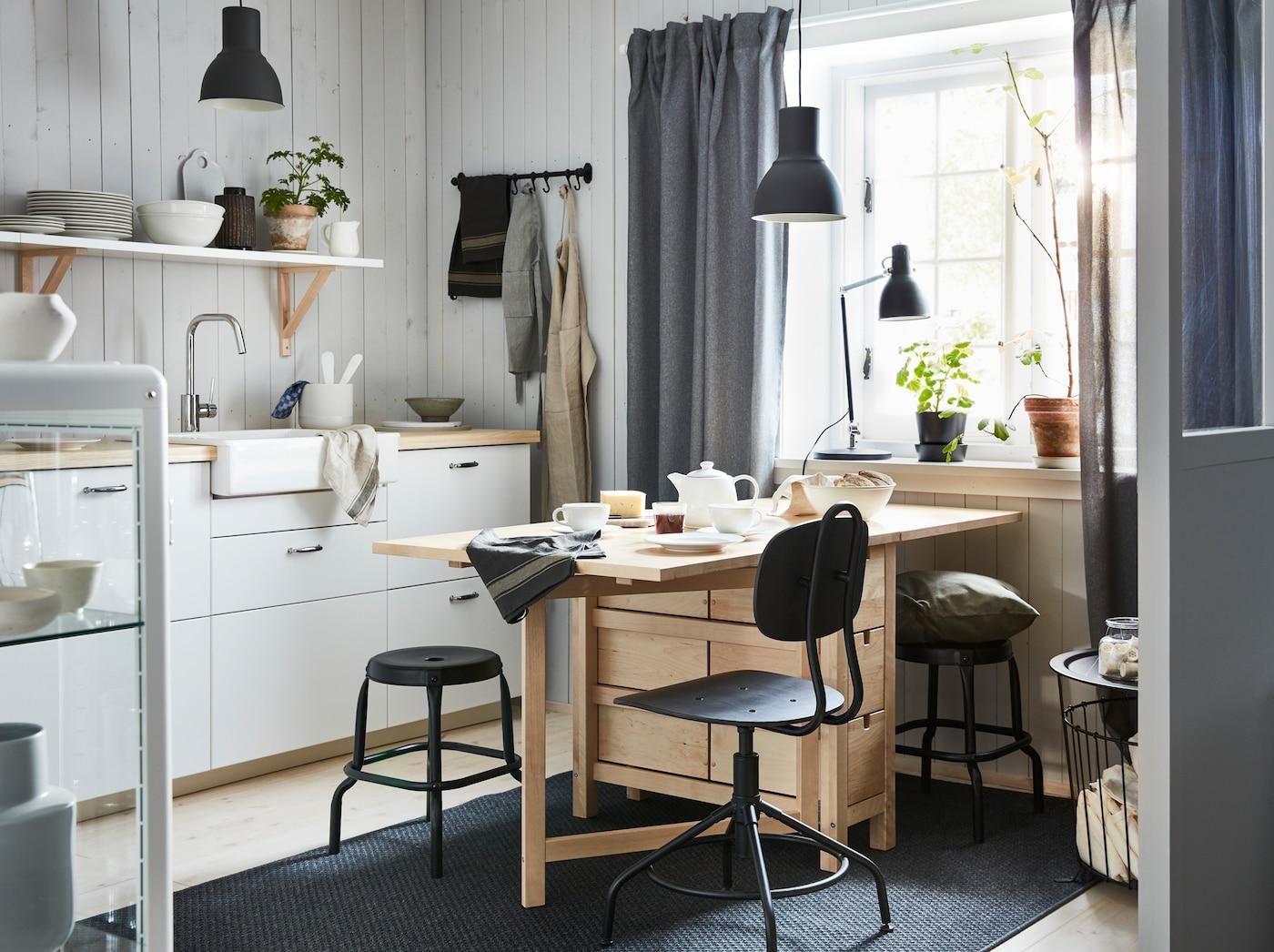 Sosnowy stół rozkładany NORDEN w małej otwartej jadalni i przestrzeni kuchennej.