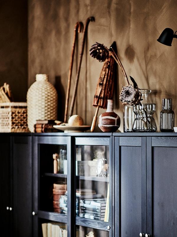Souvenir di viaggi, oggetti in materiali naturali e vasi in vetro con fiori su un mobile HAVSTA marrone scuro.
