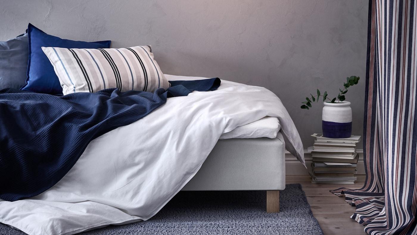 Soverom med grå vegger og ei rotete seng med ÄNGSLILJA dynetrekk, INDIRA mørkeblått sengeteppe og tre puter.