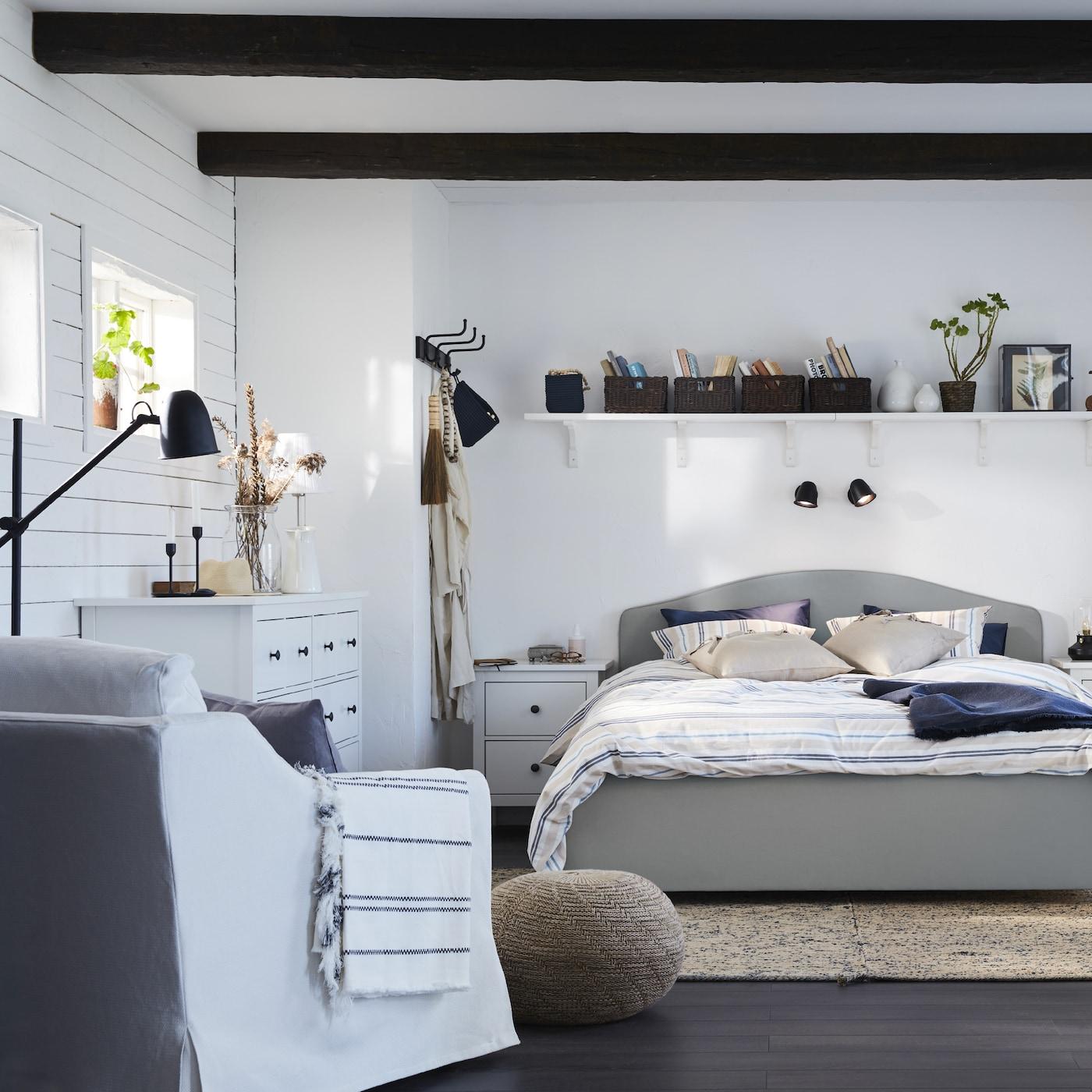 Soveværelse i en sammenhængende og traditionel stil med en beige HAUGA seng, en hvid lænestol, hvide gardiner og et mørkt blågrønt skrivebord.