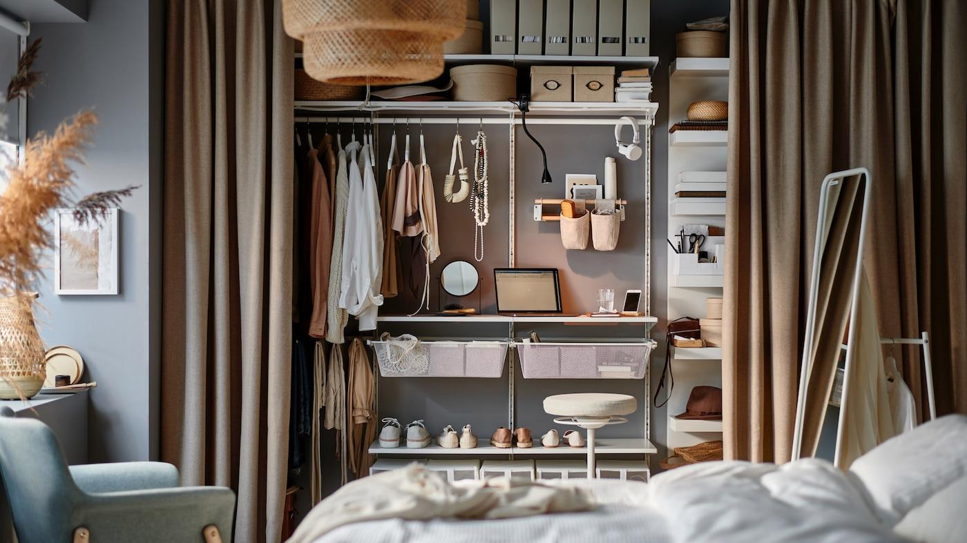 Soveværelse med en lille arbejdsstation, der består af nogle få hylder i et opbevaringssystem i en åben garderobeløsning bag gardiner.