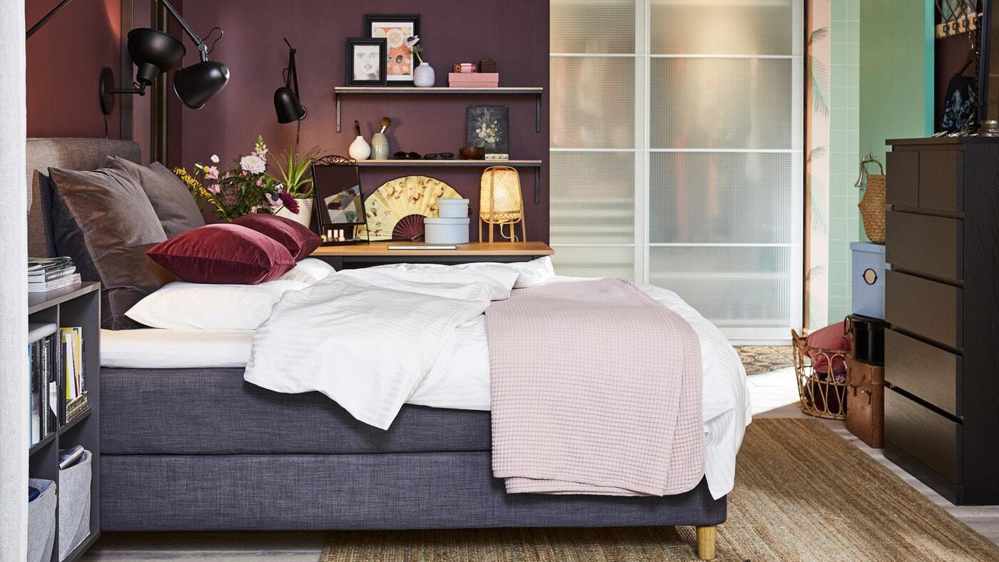 Soveværelse med en mørkegrå kontinentalseng, sorte væglamper, et tæppe af jute, en sortbrun kommode og mørkerøde pudebetræk.