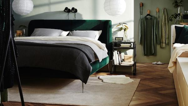 Soveværelse med et mørkegrønt TUFJORD polstret sengestel, to hvide loftlampeskærme, hvidt sengetøj og et gråt sengetæppe.