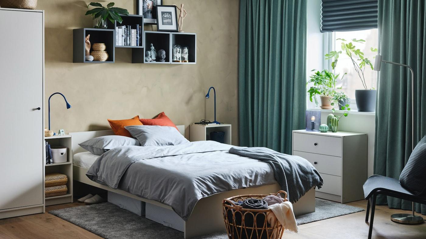 Soveværelse med et sengestel med sengegavl, et garderobeskab, et sengebord og en kommode, alt sammen i beige.
