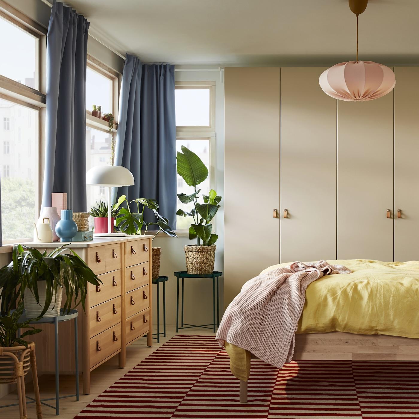 Soveværelse med et sengestel og 2 kommoder af birk, et gråbeige garderobeskab, blå gardiner og gult sengetøj.