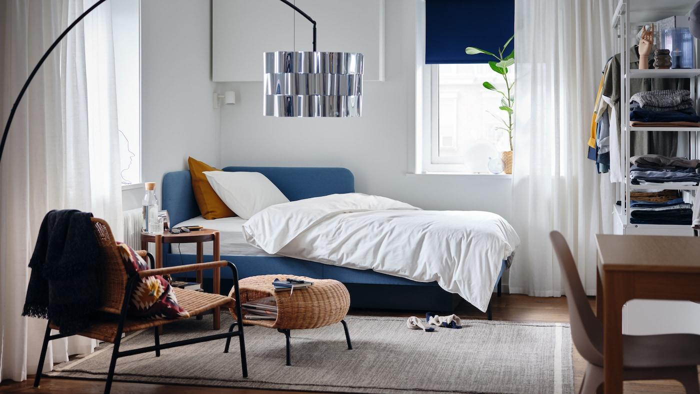 Sovrum med klädd sängstomme med hörnhuvudgavel, vitt påslakanset och krukväxt.