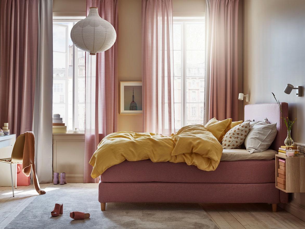 Sovrum med ljus brunrosa kontinentalsäng, gult påslakan och örngott, vita lampor och vitt toalettbord.