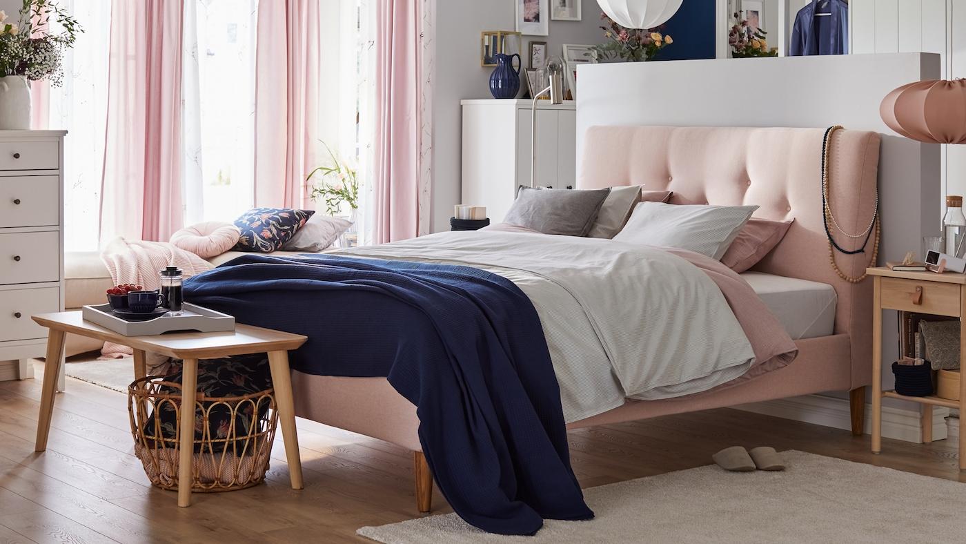 Sovrum med rosa säng med klädd sänggavel, textilier i mjuka färger, skira rosa gardiner och sidobord i trä.