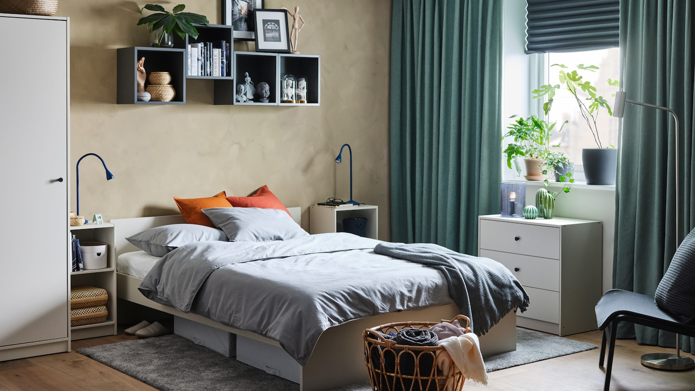 Sovrum med sängstomme med huvudgavel, garderob, sängbord och byrå i ljusbeige.