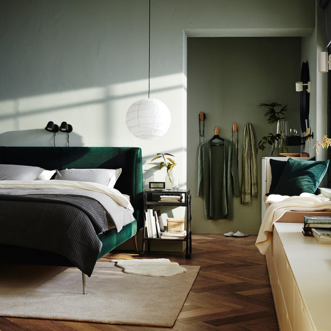 Sovrum med stoppad sängstomme i grön sammet, två svarta vägglampor, matta i off-white och vit byrå.