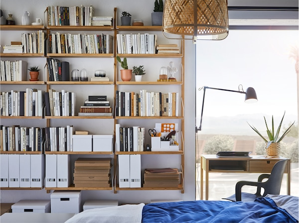 Sovrum med stor väggmonterad hyllkombination i bambu som rymmer massor av böcker, växter och prydnadsföremål.