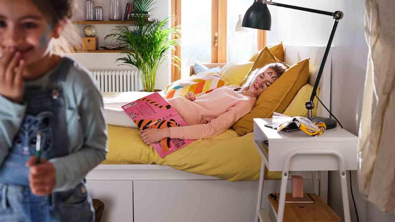 Sovrum med vit MALM sängstomme, gula påslakanset, en sovande kvinna med färg i ansiktet och ett fnittrande barn.