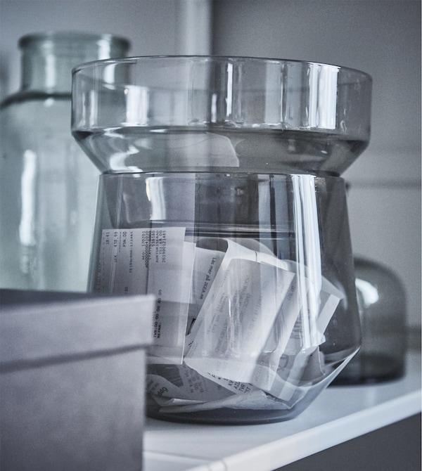 Создайте современное рабочее пространство в гостиной, избежав необходимости каждый раз убирать подальше все офисные принадлежности. Просто сложите чеки в красивую вазу, например прозрачную вазу ИКЕА ПС 2017 из серого стекла. Три жестяные банки также можно составить вместе и использовать в качестве х