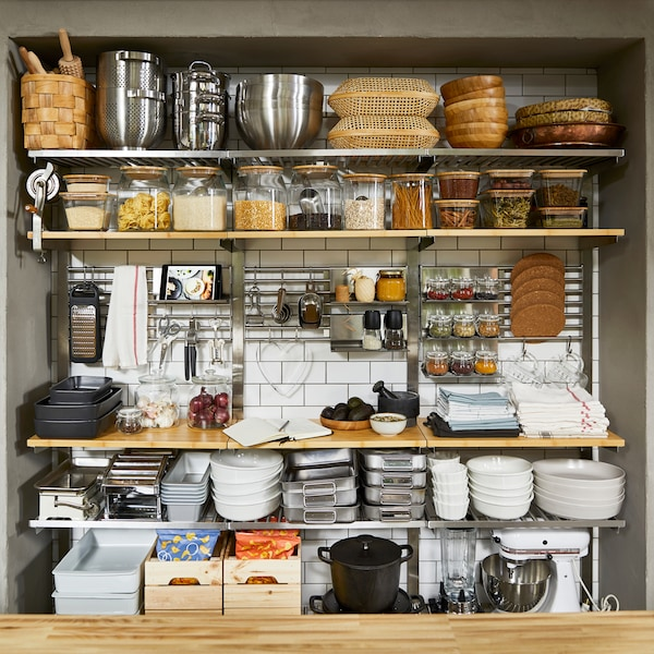 Spacious, open wall storage with shelves and wall grids in wood/ stainless steel. Kitchen utensils and food are stored here.