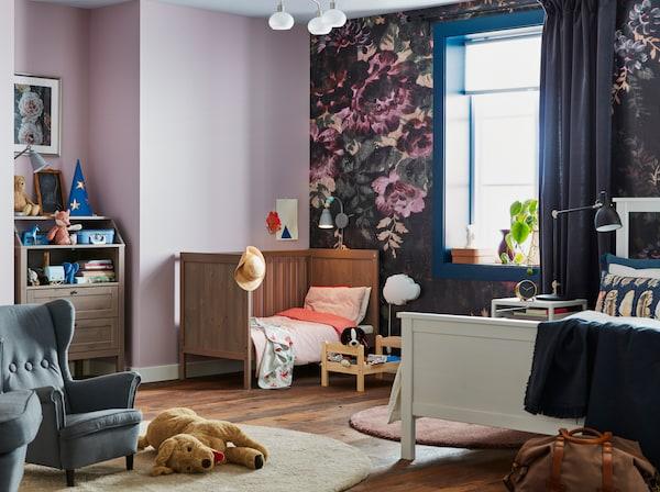 Spálňa pre rodičov s bábätkom s tapetami vo fialovej farbe a s kvetinovým vzorom a hnedou detskou postieľkou a prebaľovacím pultom IKEA SUNDVIK.
