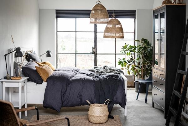 Spálňa s bielou posteľou HEMNES uprostred miestnosti, francúzskymi oknami a detailmi v prírodných materiáloch a farbách.