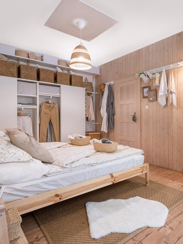 Spálňa s posteľou v prírodnom drevenom prevedení, biela šatníková skriňa a úložne boxy.