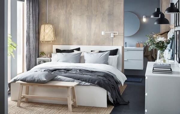 Спальня, оформленная в нейтральной цветовой гамме, с двуспальной кроватью , деревянной скамейкой и светильником с плетеным абажуром.