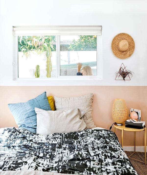 Спальня с черно-белым постельным бельем, книгами и лампами на прикроватной тумбочке, и Хлоя, проходящая мимо окна за кроватью.