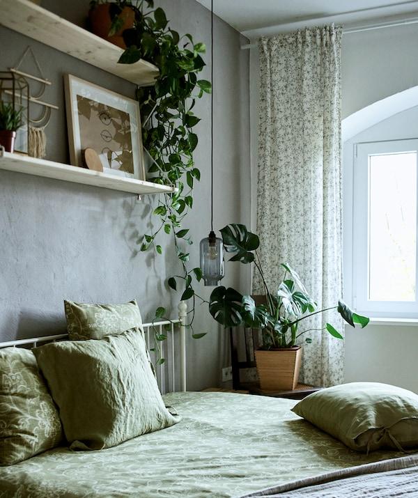 Спальня украшена зеленым текстилем, растениями и коллекцией рисунков и сувениров, расставленных на двух полках на серой стене.