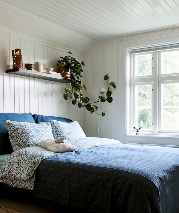 Спальня в фермерском доме с деревянной отделкой белого цвета, кровать с синим постельным бельем, над изголовьем — полка для хранения и декора.