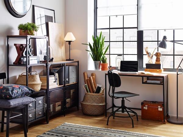 Spațiu de lucru în alb cu podele din lemn și etajere și birou FJÄLLBO - stil industrial, din metal negru și lemn, în zona ferestrei.