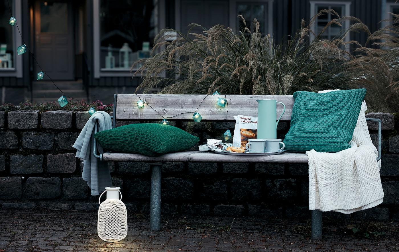 Spațiu exterior într-un cadru urban, la începutul serii, cu o bancă publică pe care se află o tavă cu cafea, perne de șezut, o pătură și lumini decorative.