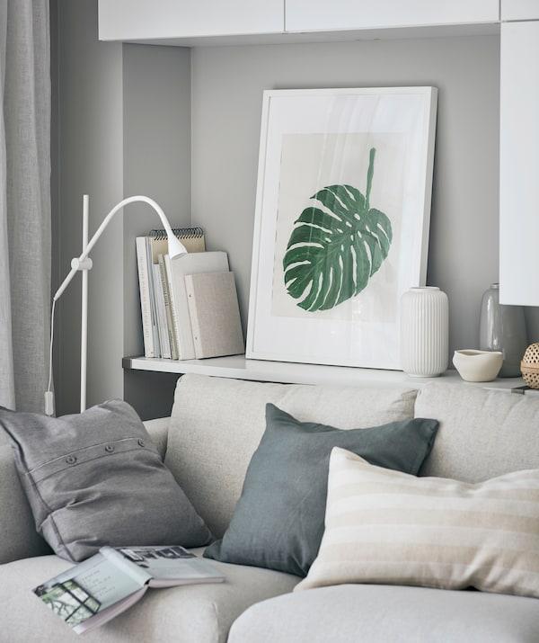 Spațiu în camera de zi cu o poliță plină cu cărți în spatele canapelei, decorațiuni și desenul înrămat al unei frunze MONSTRERA.