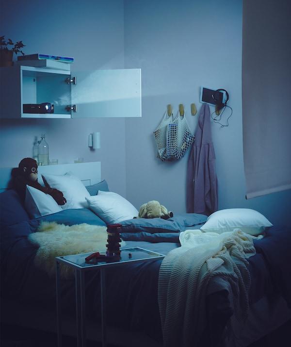 Spavaća soba, blago osvetljena projektorom na zidnoj komodi iznad kreveta, čiji snop je uperen na roletne s druge strane sobe.