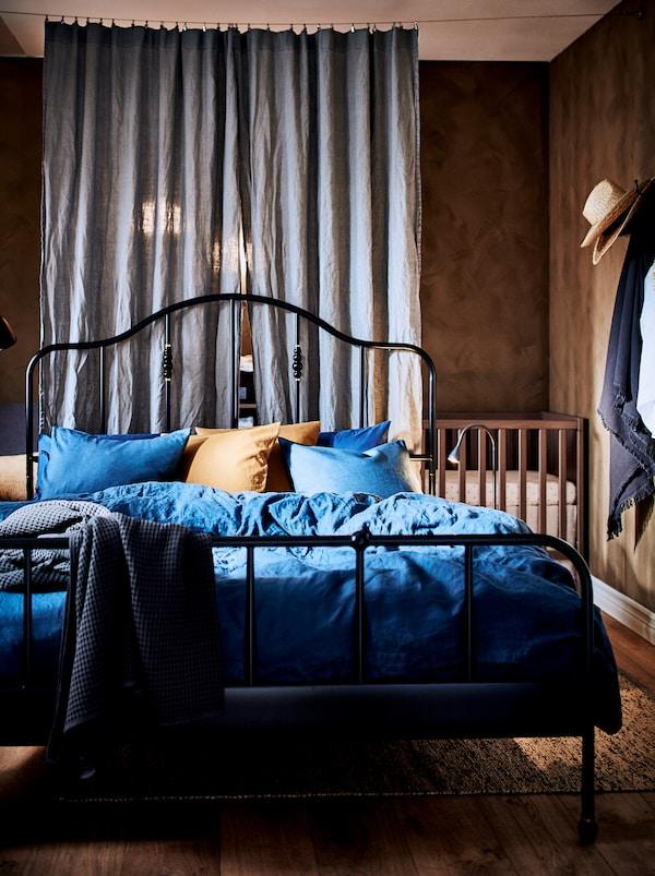 Spavaća soba blago podeljena dvema zavesama s crnim SAGSTUA metalnim krevetnim okvirom u središtu prostorije, i krevecem.