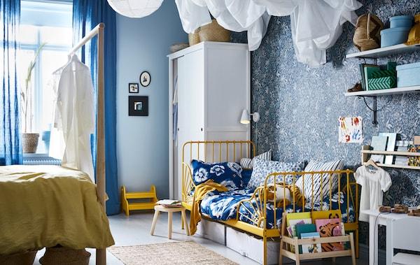 Spavaća soba plavih i žutih nijansi, s krevetom za odrasle na jednoj i dečjim krevetom na drugoj strani.