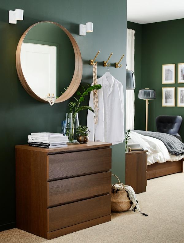 Spavaća soba s komodom s braon bajcovanim jasenovim furnirom, okruglim ogledalom, korpom od morske trave i kukama.
