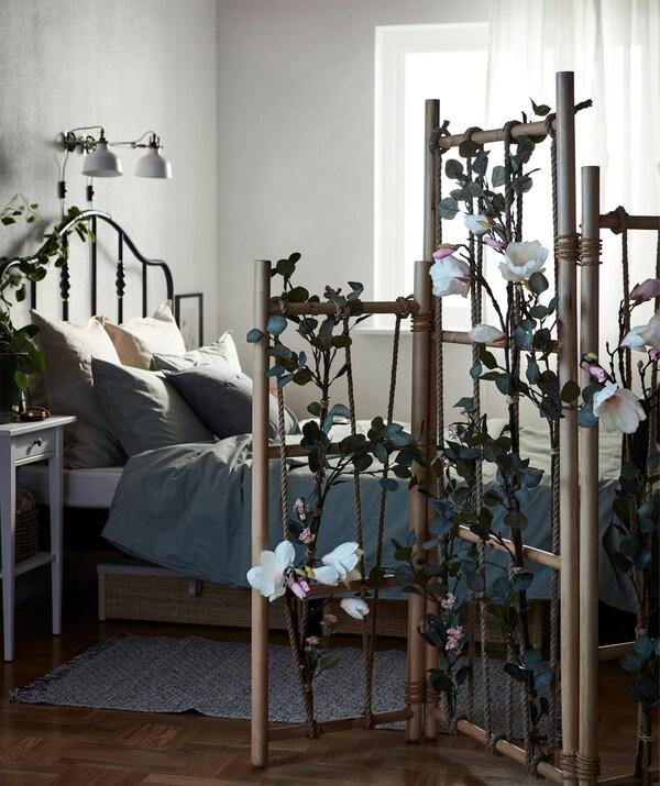 Spavaća soba s krevetom odvojenim TÄNKVÄRD paravanom naglašena je i istaknuta veštačkim zelenilom.