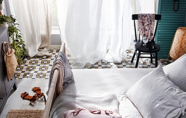 Spavaća soba s otvorenim prozorima od poda do plafona i providnim zavesama u prvom planu, koje lelujaju pod nadolazećim povetarcem.