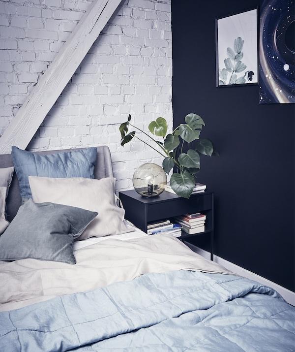 Spavaća soba sa slojevima sive posteljine, jednim crnim zidom i jednim bijelim zidom od cigle.